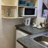 Small kitchenette with fridge, microwave, utensils, kettle, braai utensils